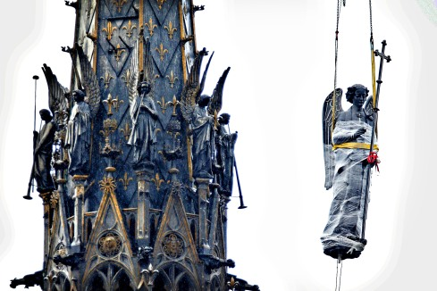 The restored statue archange Saint Michel is lifted up next to t