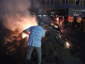"Farmers and breeders set fire to manure, tyres and wooden pallets they dumped outside the prefecture building in downton Rennes, northwestern France, on July 2, 2015, staging a protest they named ""Night of Distress"" demanding simplification of their bureaucratic tasks with the European Union regarding subsidies, and protesting the fall of prices. The inscription on the jersey reads ""Stop taking us for fools"". AFP PHOTO / DAMIEN MEYER"