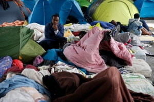 Migrants from Eritrea sit near tents as they live in a make-shift camp under a metro bridge in Paris, France, May 28, 2015. African migrants, principally from Eritrea and Sudan, sleep rough in some 80 tents and shelters as they make their way from the Mediterranean northwards towards Calais. REUTERS/Benoit Tessier - RTX1EXEQ