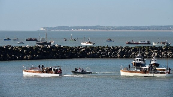 'Little Ships' begin their journey across the English Channel, with Dover seen behind, at Ramsgate harbour in south east England, May 21 , 2015. Over fifty 'Little Ships', used in action in 1940, sailed to Dunkirk in northern France to mark the seventy fifth anniversary of Operation Dynamo in World War II when a mass evacuation took place of Allied troops as German forces advanced through France. REUTERS/Toby Melville - RTX1DXGA