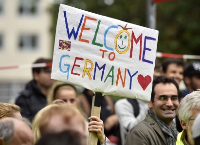 People welcome refugees with a banner reading 'welcome to Germany' in Dortmund, Germany, Sunday, Sept. 6, 2015, where thousands of migrants and refugees arrived by trains. (AP Photo/Martin Meissner)/MME130/303010942473/1509061734