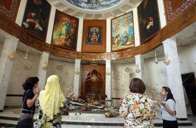Iraqi Christian women pray in front of the damaged altar at the Sayidat al-Nejat Catholic Cathedral, or Syrian Catholic Church, in central Baghdad on November 3, 2010 after US and Iraqi forces stormed on October 31 the cathedral to free dozens of hostages in an attack claimed by Al-Qaeda gunmen and in which 46 worshippers were killed. AFP PHOTO/AHMAD AL-RUBAYE