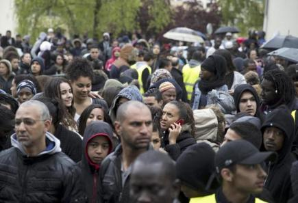 People gather on May 2, 2015, following the death of a 14-year-old boy, in Trappes, west of Paris. Relatives of 14-year-old Moussa, shot dead the day before, arrived for a public meeting organised by the city's mayor, in Trappes. The teenager was killed, and another lightly wounded, in a shooting on May 1 in Trappes, a working class suburb of Paris, where fights and score-settlings have occured in recent weeks. AFP PHOTO / KENZO TRIBOUILLARD