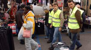 A recent photo taken March 3, 2009 shows volunteers with fluorescent vests, as they walk in a market during a citizen's patrol in Padova, north-east Italy. Groups of unarmed volunteers, including both men and women have joined with police to patrol in some Italian cities, after Italy's conservative government approved tougher measures to crack down on sexual violence and illegal immigration as a recent spate of violent crimes has caused anxiety among the Italian public. AFP PHOTO / PAOLO BALANZA