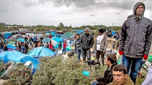 "People stand at a site dubbed the ""New Jungle"", where some 3,000 people have set up camp -- most seeking desperately to get to England, in Calais on September 21, 2015. The slum-like migrant camp sprung up after the closure of notorious Red Cross camp Sangatte in 2002, which had become overcrowded and prone to violent riots. However migrants and refugees have kept coming and the ""New Jungle"" has swelled along with the numbers of those making often deadly attempts to smuggle themselves across the Channel. AFP PHOTO / PHILIPPE HUGUEN"