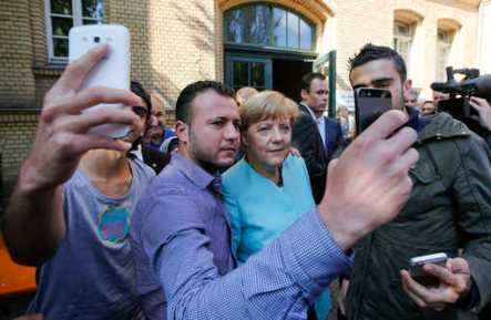Migrants from Syria and Iraq take selfies with German Chancellor Angela Merkel outside a refugee camp near the Federal Office for Migration and Refugees after their registration at Berlin's Spandau district, Germany, September 10, 2015. REUTERS/Fabrizio Bensch - RTSG4Y