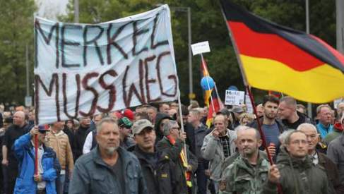 """DRESDEN, GERMANY - OCTOBER 03: Supporters of the Pegida movement march with German flags and a sign that reads: """"Merkel must go,"""" in reference to German Chancellor Angela Merkel, on German Unity Day on October 3, 2016 in Dresden, Germany. Unity Day, called Tag der Deutschen Einheit, commemorates German reunification of East and West Germany following the end of the Cold War. This year's main celebrations are taking place in Dresden and are being accompanied by protests from both left and right-wing groups, notably the anti-Muslim and anti-immigration Pegida, which has its roots in Dresden, as well as extraordinary security measures by police. (Photo by Sean Gallup/Getty Images)"""
