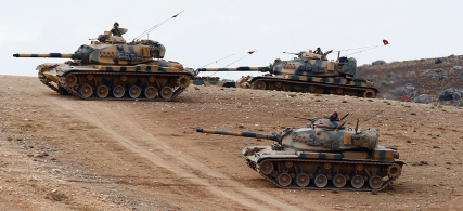 Turkish army tanks take up position on the Turkish-Syrian border near the southeastern town of Suruc in Sanliurfa province September 29, 2014. Turkish tanks and armoured vehicles took up positions on hills overlooking the besieged Syrian border town of Kobani on Monday as shelling by Islamic State insurgents intensified and stray fire hit Turkish soil, a Reuters correspondent said. At least 30 tanks and armoured vehicles, some with their guns pointed towards Syrian territory, were positioned near a Turkish military base just northwest of Kobani. Plumes of smoke rose up as shells hit the eastern and western sides of Kobani and sporadic bursts of machinegun fire rang out. REUTERS/Murad Sezer (TURKEY - Tags: POLITICS CONFLICT CIVIL UNREST MILITARY) - RTR487NC