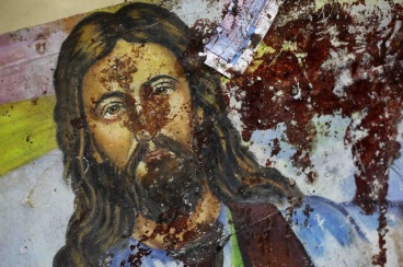 A blood-spattered poster of Jesus Christ is seen inside the the Coptic Christian Saints Church in the Mediterranean port city of Alexandria, Egypt Saturday, Jan. 1, 2011. A car exploded in front of the church early Saturday as worshippers emerged from a New Year's Mass, killing at least 21 people according to officials, and sparking clashes between Christians and Muslims _ a sign of the sectarian anger that has been arising with greater frequency in Egypt. (AP Photo/Ben Curtis)