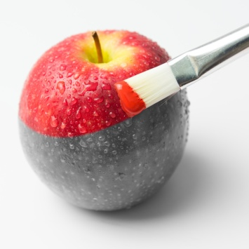 Painting a fresh red apple with paintbrush