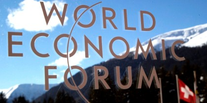 The logo of the Forum is seen through a window with the alps in the background during the World Economic Forum in Davos, Switzerland, Wednesday, Jan. 22, 2014. The World Economic Forum is opening today where world's financial and political elite will meet in the next four days in Davos. (AP Photo/Michel Euler)
